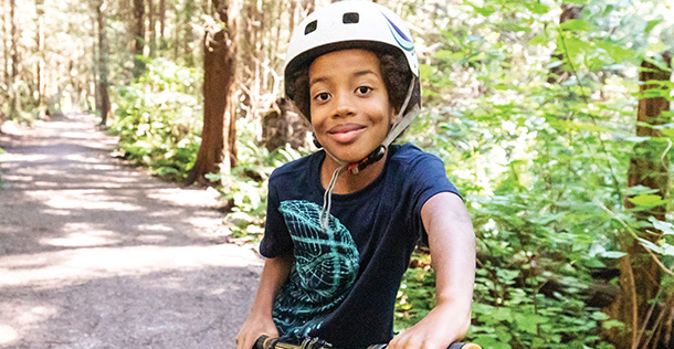 A young boy wearing a helmet on a bike in the woods