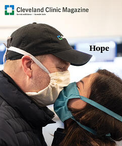 Two people wearing face masks kissing in an airport