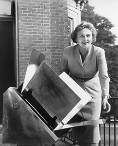 Maria Telkes, PhD in a black and white image posing by a device