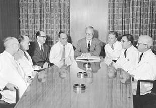 a group of medical professionals around a table looking at a book