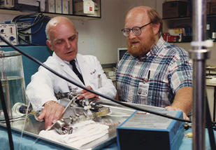 Dr. Golding (left) and biomedical engineer William Smith looking at medical equipment