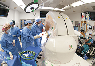 multiple doctors in an operating room with a white medical machine